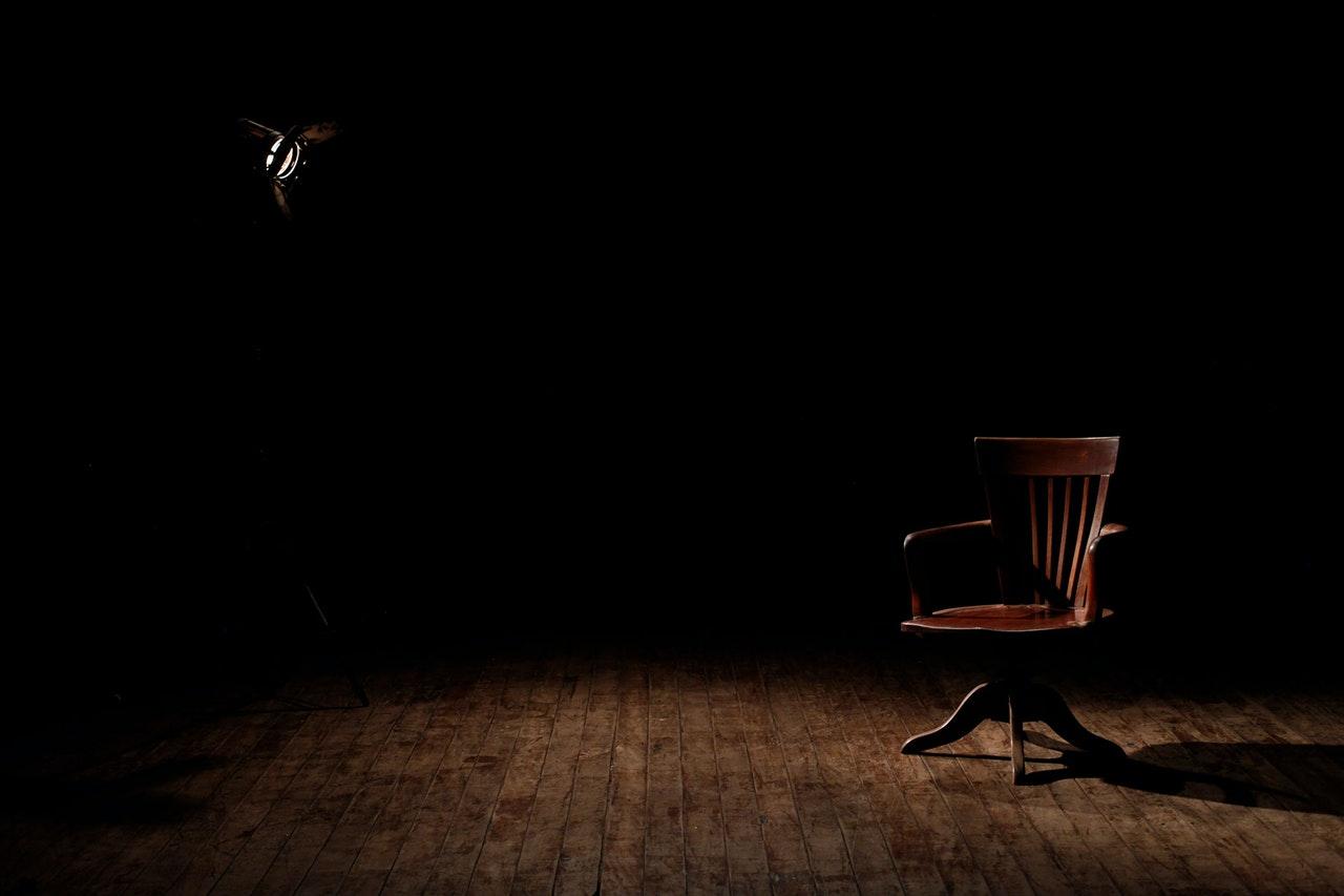 Podium Derailers - chair in dark room
